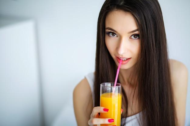 Beiläufige lächelnde frau, die ein glas orangensaft anhält