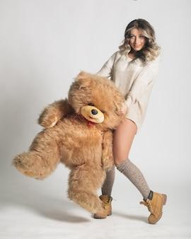 Beiläufige lächelnde junge frau in der gestrickten kleidung, die großen weichen teddybären anhält