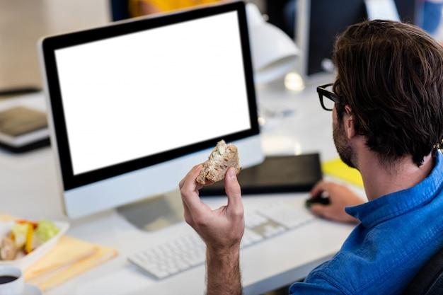 Beiläufiger geschäftsmann, der ein sandwich isst