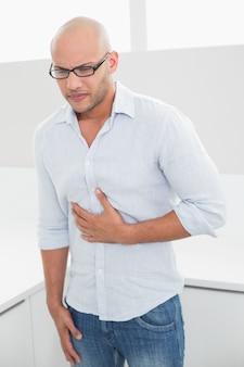Beiläufiger mann, der zu hause unter schmerz in der brust leidet