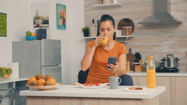 Beim frühstück ein glas frischen orangensaft genießen und auf dem smartphone surfen. frau, die gesunden und natürlichen orangensaft trinkt. hausfrau trinkt gesunden, natürlichen, hausgemachten orangensaft. aktualisierung