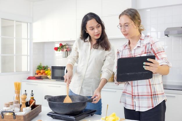Beim kochen in der küche sucht ein glückliches paar mit einem smart-tablet online nach einem rezept.