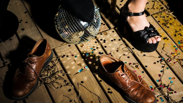 Bein der frau im schuh nahe discoball und -stiefeln