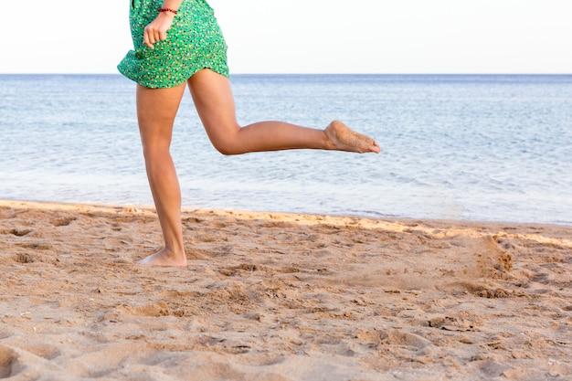 Bein der frau laufend auf sandstrand. sommerurlaub. glückliche schöne frau am strand laufen