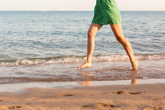 Bein der frau laufend auf strand mit dem wasserspritzen