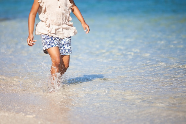 Bein des mädchens des kleinen kindes laufend auf strand mit dem wasser, das in den sommerferien spritzt