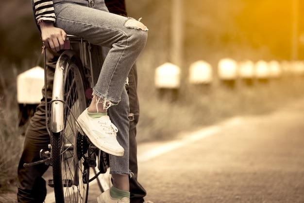 Bein und füße der jungen paare, die zusammen fahrrad im weinlesefarbton fahren