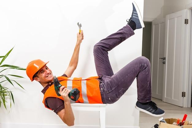 Bein und gelber helm des verletzten liegenden arbeiters bei der arbeit.