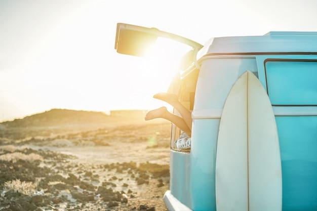 Beinansicht des glücklichen surfermädchens innerhalb des minivans bei sonnenuntergang - junge frau, die spaß auf sommerferien hat - reise-, sport- und naturkonzept - fokus auf füße