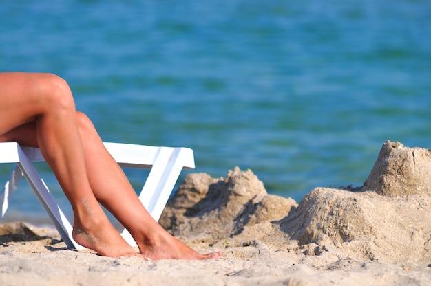 Beine der frau auf sonnenliege am sandstrand nahe stillem meerwasserrand am sonnigen sommertag. konzept für glück, urlaub und freiheit