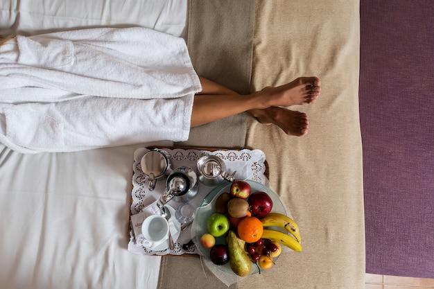Beine der frau, die auf bett mit teller der früchte liegt