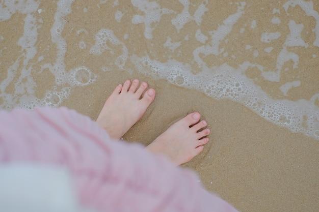 Beine der frau entspannen sich im rosa kleid auf einem strandseesand und -welle im sommer.