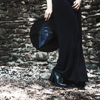 Beine der frau im schwarzen kleid, das hut hält