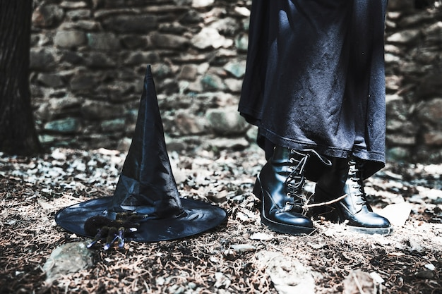 Beine der frau im schwarzen kleid mit hut auf dem boden