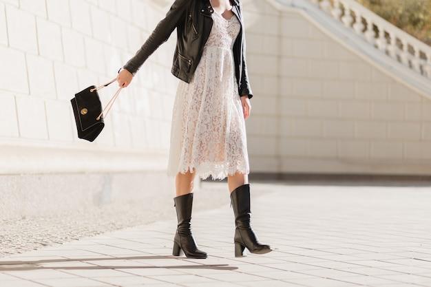 Beine der jungen hübschen frau in den stiefeln, die im modischen outfit auf der straße gehen, geldbörse halten, schwarze lederjacke und weißes spitzenkleid tragen, frühlingsherbststil