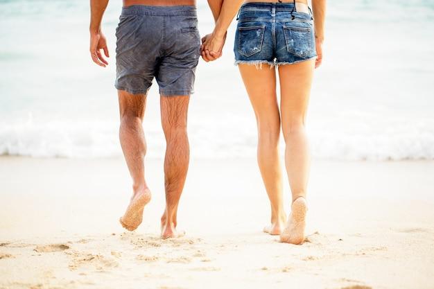 Beine der jungen paar zu fuß auf sand am meer