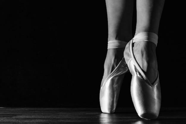 Beine der klassischen ballerina der nahaufnahme in pointes auf dem schwarzen boden