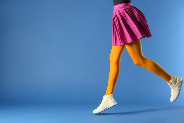 Beine der schönen jungen frau, die strumpfhosen und rock auf blau trägt