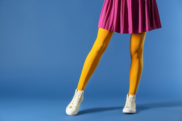 Beine der schönen jungen frau, die strumpfhosen und rock auf farbe trägt