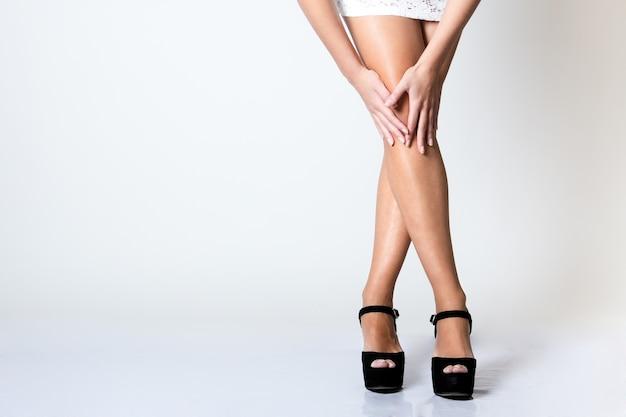Beine der schönen jungen frau posiert mit weißen bildschirm