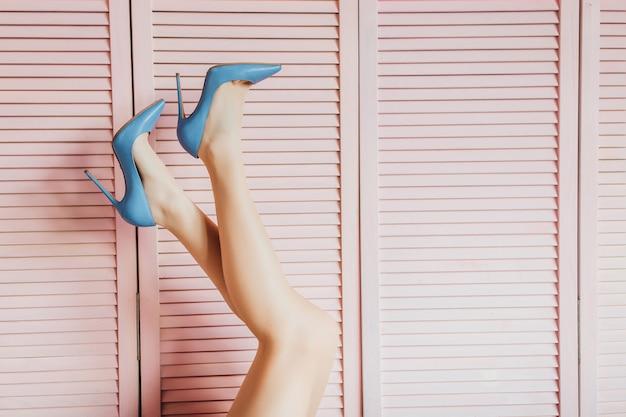 Beine der schönheitsfrau auf rosa.