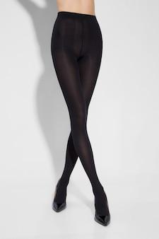 Beine der sexy jungen kaukasischen frau in den schwarzen nylonstrumpfhosen auf grauem hintergrund