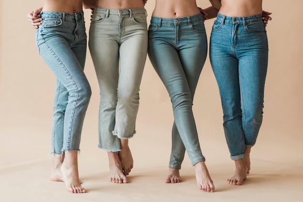 Beine der tragenden jeans der weiblichen gruppe, die in den verschiedenen haltungen stehen
