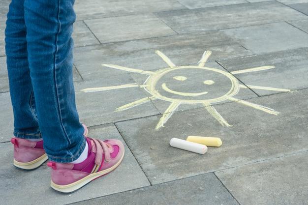 Beine des kindes mit gemaltem symbol der sonne