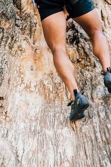 Beine des mannes auf felsen klettern