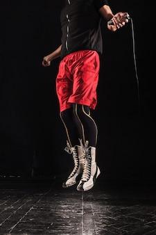 Beine des muskulösen mannes mit springseil