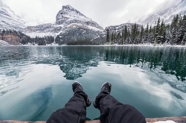 Beine des reisenden entspannend auf pier mit rocky mountains reflexion im lake o'hara im winter im yoho national park, kanada