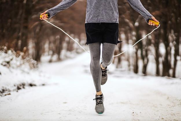 Beine des sportlers, der das seil im wald am verschneiten wintertag springt.
