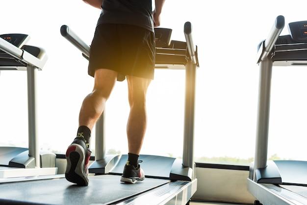 Beine des sportlers laufend auf tretmühle in der eignungsturnhallenmitte. sport und gesundes lebensstilkonzept.