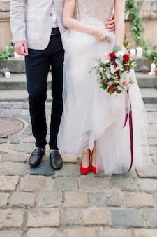 Beine des stilvollen hochzeitspaares, bräutigam in schwarzen schuhen und braut in roten fersenschuhen mit einem luxuriösen hochzeitskleid, das hochzeitsstrauß hält. außenaufnahme in der antiken stadt.