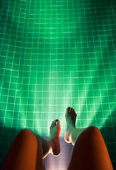 Beine, die das pool-helle glühen hängen