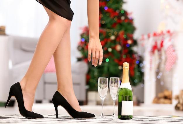 Beine einer frau in high heels schuhen und champagner zu hause