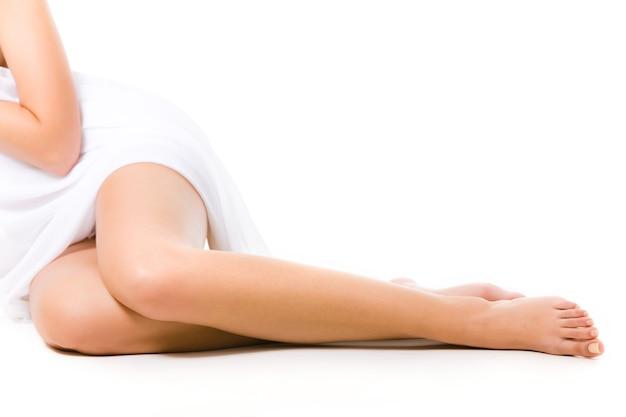 Beine einer jungen frau, die sitzt und ihren körper mit einem weißen vorhang bedeckt