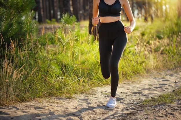 Beine einer laufenden sportlerin auf einer sandigen straße im wald. zurück sonne