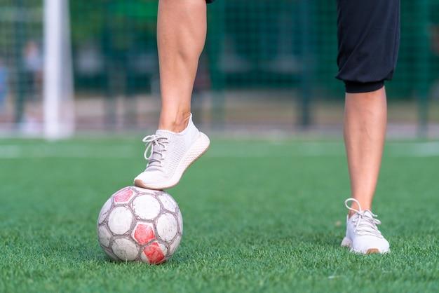 Beine einer muskulösen jungen frau mit fuß auf einem ball