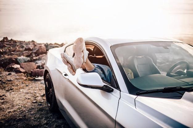 Beine eines jungen mädchens in weißen stiefeln in einem autofenster auf einem hintergrund der küste des meeres, flach liegend. genuss, entspannung im tourismus, reisen, freizeit, ruhe, das konzept des glücks.