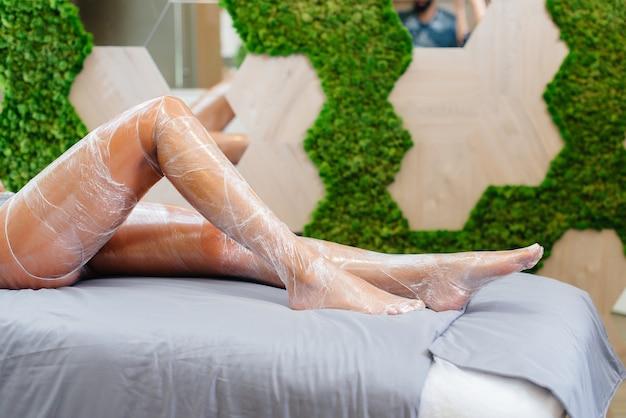 Beine eines jungen mädchens nahaufnahme während eines kosmetischen eingriffs in einem modernen schönheitssalon.