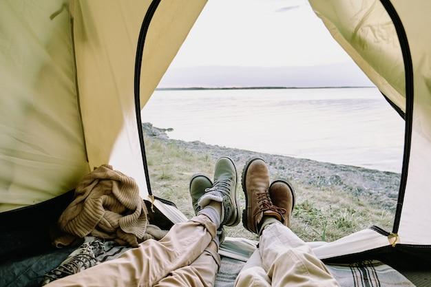 Beine eines jungen verliebten paares in freizeitkleidung, die im offenen zelt vor dem meer liegen und sich beim wandern am sommerwochenende entspannen