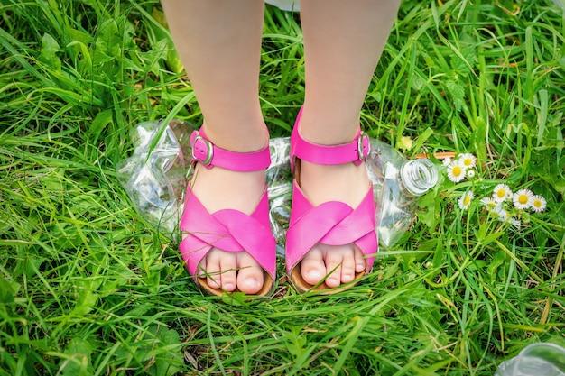 Beine eines kleinen mädchens zertrampelt eine plastikflasche