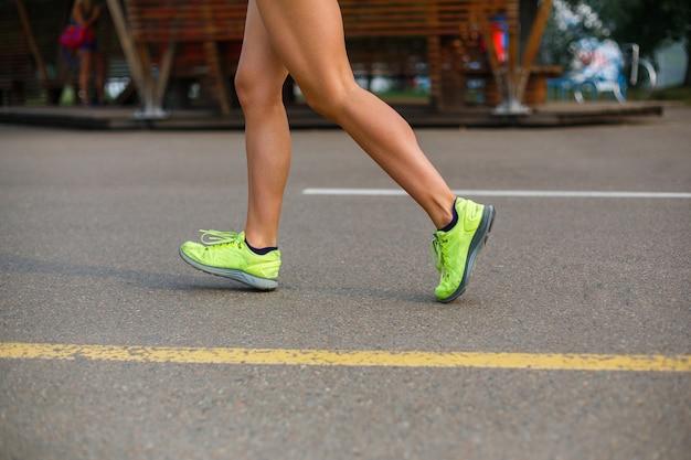 Beine eines laufenden athletischen mädchens in grünen turnschuhen