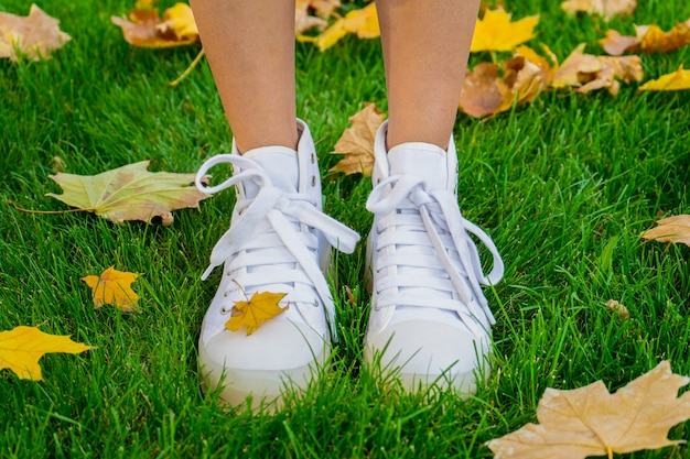 Beine eines mädchens im herbstpark in weißen schuhen auf einem grünen rasen