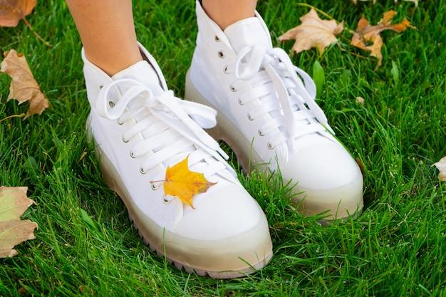 Beine eines mädchens in weißen stiefeln in einem park auf grünem gras