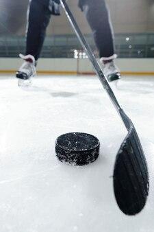 Beine eines männlichen hockeyspielers in sportuniform und schlittschuhen, die auf der eisbahn gegen die stadionumgebung stehen, während sie puck schießen