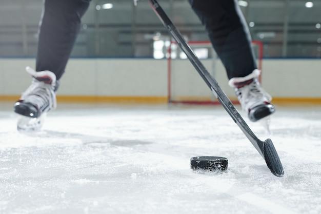 Beine eines männlichen hockeyspielers in sportuniform und schlittschuhen, die sich vor der kamera gegen die stadionumgebung bewegen, während sie puck schießen