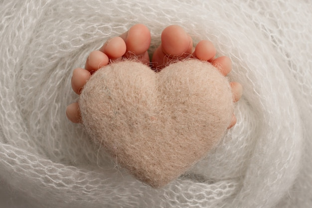 Beine eines neugeborenen babys, weiche gestrickte decke in grauweißer farbe, gestricktes grauweißes herz, schwarz-weiße studiofotografie. foto in hoher qualität