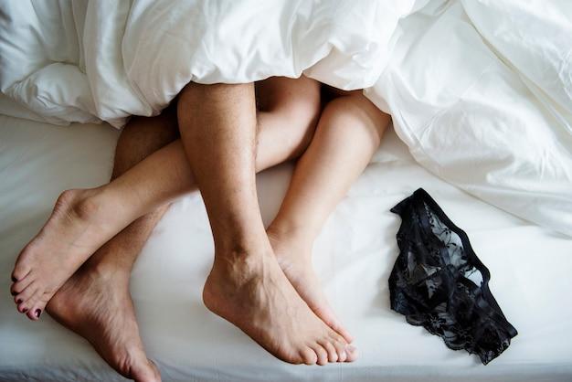 Beine eines paares, das im bett schläft